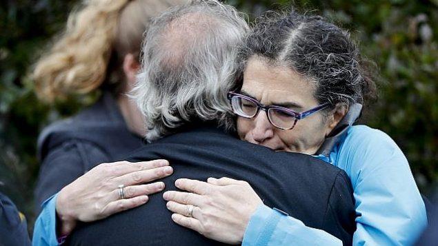 الناس يتعانقون على طول الشارع في حي تلة سكويرل في بيتسبرغ حيث أطلق مهاجم النار خلال الصلاة في كنيس شجرة الحياة يوم السبت 27 أكتوبر، 2018. (AP/Keith Srakocic)