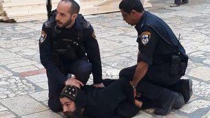 ضباط شرطة إسرائيل يكبحون رجل دين قبطيا خلال احتجاج على أعمال صيانة للسلامة في كنيسة القيامة في مدينة القدس القديمة، 24 أكتوبر / تشرين الأول 2018.  (Patriarchate of the Orthodox Copts in Jerusalem/Facebook)
