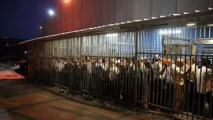 عمال فلسطينيون يقفون في انتظار اجتياز حاجز للعمل في إسرائيل عند الجدار الأمني في مدينة بيت لحم في الضفة الغربية، 23 أغسطس، 2010.  (Najeh Hashlamoun/Flash 90)