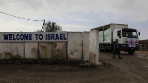 جنود من الأمم المتحدة يراقبون مرور شاحنة تابعة للصليب الأحمر محملة بالتفاح عبر معبر القنيطرة من إسرائيل إلى داخل سوريا، فبراير 2011.  (Tsafrir Abayov/Flash90)