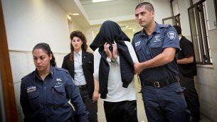 ضابط شرطة الحدود بن درعي، الذي أدين فيما بعد بقتل مراهق فلسطيني يبلغ من العمر 17 عاماً في بلدة بيتونيا بالضفة الغربية في عام 2014، يغطي وجهه أثناء دخوله جلسة استماع في محكمة مقاطعة القدس في 7 ديسمبر / كانون الأول ، 2014. (Miriam Alster/Flash90)