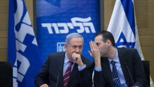 رئيس الوزراء بنيامين نتنياهو يتحدث مع عضو الكنيست ميكي زوهار خلال جلسة لحزب الليكود في الكنيست، 25 يناير 2016 (Yonatan Sindel/Flash90)