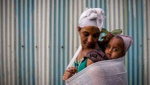 إمرأة في جماعة الفلاشا اليهودية الإثيوبية تحمل طفلها على ظهرها قبل حضور الصلاة في عيد الفصح، في الكنيس في غوندار، إثيوبيا. 22 أبريل 2016. (Miriam Alster/FLASH90)