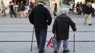 زوجان مسنان يمشيان في شارع يافا في وسط القدس يوم 20 فبراير 2017. (Nati Shohat/Flash90)