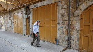 رجل فلسطيني يمر من أمام محلات تجارية مغلقة في البلدة القديمة في مدينة الخليل بعد الإعلان عن إضراب عام احتجاجا على قانون الدولة القومية الإسرائيلي، 1 أكتوبر، 2018.(Wisam Hashlamoun/Flash90)