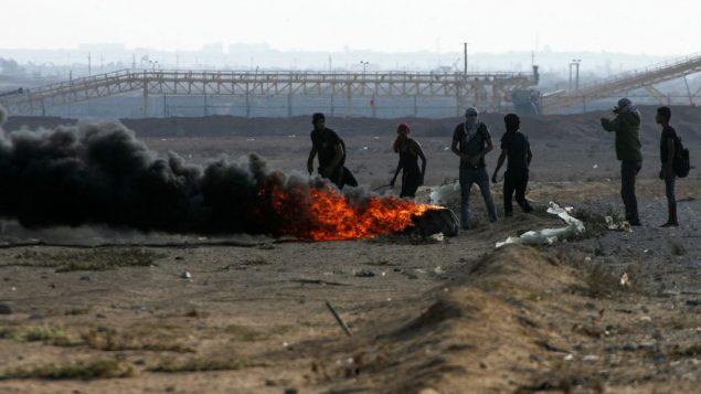 متظاهرون فلسطينيون يحرقون إطارات خلال مظاهرات 'مسيرة العودة'، عند الحدود بين اسرائيل وقطاع غزة، في رفح، 12 اكتوبر 2018 (Abed Rahim Khatib/Flash90)