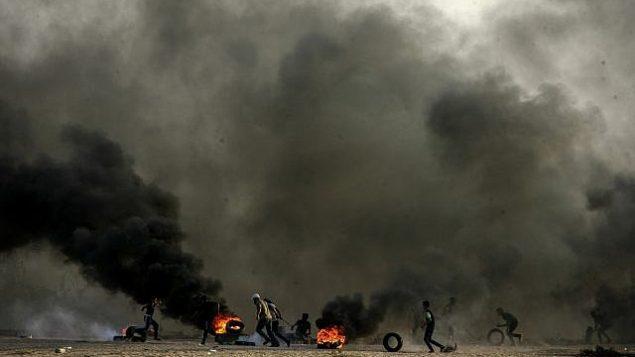 """فلسطينيون يشعلون إطارات في احتجاجات خلال """"مسيرة العودة"""" على حدود غزة-إسرائيل في رفح، قطاع غزة في 12 أكتوبر، 2018. (Abed Rahim Khatib/Flash90)"""