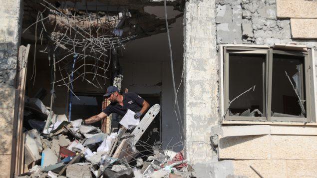 قوات الأمن الإسرائيلي تتفقد مبنى أصيب بصاروخ تم إطلاقه من قطاع غزة تجاه مدينة بئر السبع في جنوب إسرائيل، 17 أكتوبر، 2018. (Yonatan Sindel/Flash90)