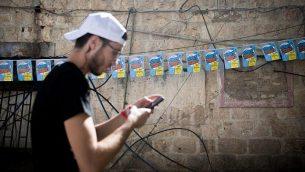 رجل يقف امام ملصقات للمرشح لرئاسة بلدية القدس يوسي ديتش امام سوق محانيه يهودا في القدس، 29 اكتوبر 2018 (Yonatan Sindel/Flash90)