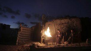 في هذه الصورة من 15 يناير، 2017، عائلة فلسطينية تحاول أن تتدفا حول النار خارج منزل من الصفيح خلال انقطاع للكهرباء في مدينة خان يونس في جنوب قطاع غزة.  (AP Photo/ Khalil Hamra)