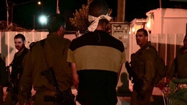 جنود اسرائيليون يعتقلون مشتبه به بطعن جندي احتياط امام قاعدة عسكرية اسرائيلية في شمال الضفة الغربية، 12 اكتوبر 2018 (Nasser Ishtayeh/Flash90)