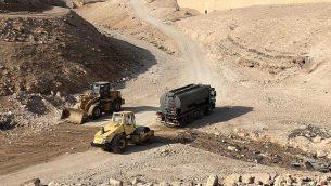 جرافة إسرائيلية وشاحنة لنقل مياه المجارير تقومان بتنظيف طريق في الخان الأحمر تمهيدا لهدم القرية في 15 أكتوبر، 2018. (Christine Rinawi)
