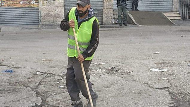 عامل نظافة تابع لبلدية القدس يقوم بتنظيف شارع في مخيم شعفاط في 23 أكتوبر، 2018. (بلدية القدس)