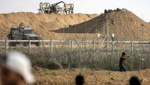 فلسطيني يستخدم المقلاع لإلقاء حجارة باتجاه القوات الإسرائيلي على الجانب الآخر من السياج الحدودي خلال مواجهات حدودية مع إسرائيل في شرق مدينة غزة، 13 يوليو، 2018. (AFP PHOTO / MAHMUD HAMS)