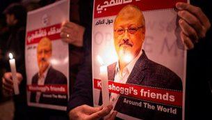 يحمل الناس ملصقات تصور الصحفي السعودي جمال خاشقجي والشموع خلال تجمع خارج القنصلية السعودية في اسطنبول، في 25 أكتوبر 2018. (Yasin Akgul/AFP)