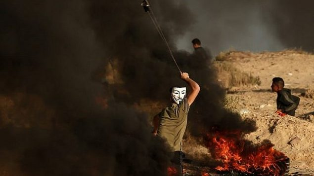 فلسطييني يستخدم المقلاع لإلقاء حجارة خلال مظاهرة على الشاطئ بالقرب من الحدود البحرية مع إسرائيل، في بيت لاخيا في جنوب قطاع غزة، 29 أكتوبر، 2018. (MAHMUD HAMS / AFP)