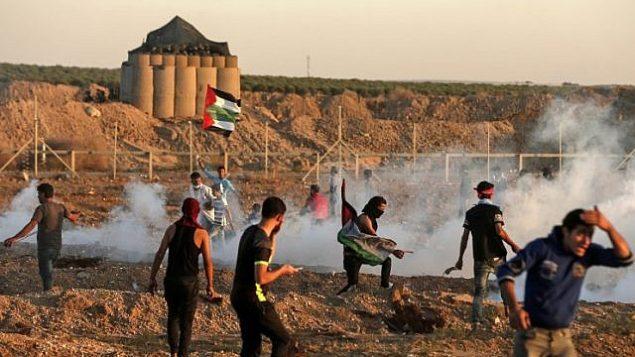 رد الفلسطينيين على الغاز المسيل للدموع الذي أطلقته القوات الإسرائيلية خلال اشتباكات شرق مدينة غزة بالقرب من الحدود بين قطاع غزة وإسرائيل في 2 نوفمبر 2018. (Mahmud Hams/AFP)