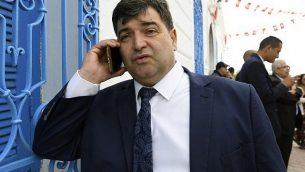 في هذه الصورة التي تم  التقاطها في 2 مايو، 2018، روني طرابلسي يتحدث بالهاتف خارج كنيس الغريبة في جزيرة جربة السياحية في تونس.  (FETHI BELAID / AFP)