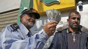 فلسطيني يعرض أمواله بعد تلقي راتبه في رفح جنوب قطاع غزة في 9 نوفمبر 2018. (Said Khatib/AFP)