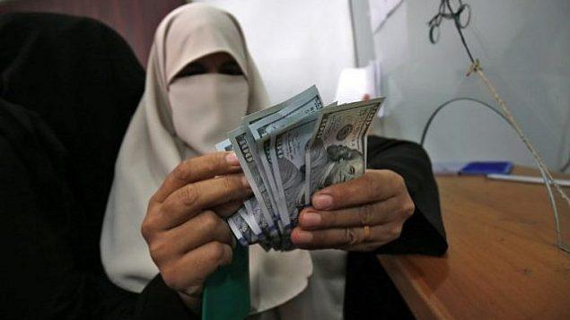 امرأة فلسطينية تقوم بعد المال بعد تلقيها راتبها في رفح في جنوب قطاع غزة، 9 نوفمبر، 2018. (Said Khatib/AFP)