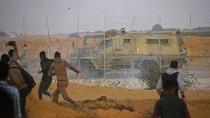 صورة توضيحية: الفلسطينيون يلقون بالحجارة على سيارة تابعة للجيش الإسرائيلي خلال اشتباكات بين إسرائيل وخان يونس في جنوب قطاع غزة في 9 نوفمبر / تشرين الثاني 2018. (Said Khatib/AFP)