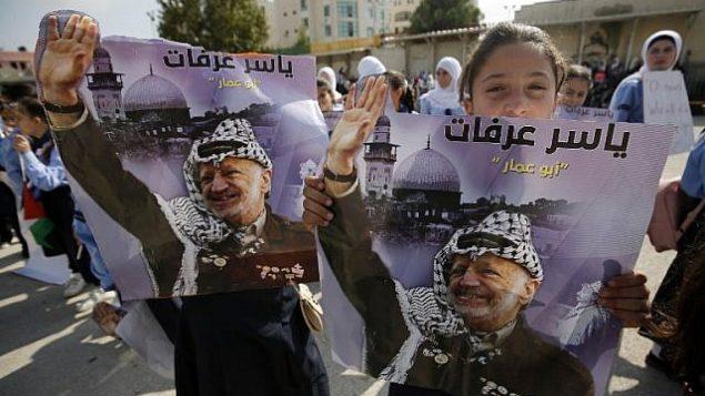 فتاة تحمل صورة الزعيم الراحل ياسر عرفات بينما يحتفل الفلسطينيون بالذكرى الرابعة عشرة لوفاته في مدينة رام الله بالضفة الغربية، في 11 نوفمبر / تشرين الثاني 2018. (ABBAS MOMANI/AFP)