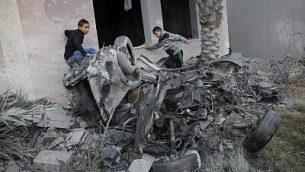 فلسطينيون يقفون بالقرب من مركبة، ورد أنه تم تدميرها في أعقاب غارة جوية إسرائيلية في خان يونس في جنوب قطاع غزة، 12 نوفمبر، 2018. (Photo by SAID KHATIB / AFP)