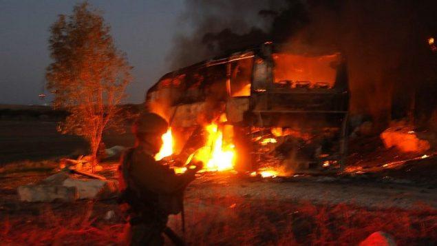 قوى الأمن وطواقم الإطفاء الإسرائيلية تحتشد بالقرب من حافلة مشتعلة بعد إصابتها بصاروخ مضاد للدبابات تم إطلاقه من القطاع الفلسطيني، على حدود إسرائيل-غزة بالقرب من كيبوتس كفار عزة، 12 نوفمبر، 2018. (Menahem KAHANA / AFP)