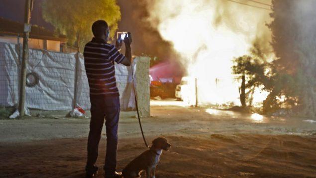 رجل يشاهد مبنى يحترق نتيجة اصابته بصاروخ اطلق من قطاع غزة، في بلدة سديروت جنوب اسرائيل، 12 نوفمبر 2018 (Menahem KAHANA / AFP)