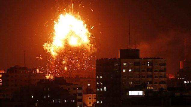 النيران فوق مبنى يحوي مقر قناة الاقصى في غزة خلال غارة جوية اسرائيلية، 12 نوفمبر 2018 (MAHMUD HAMS / AFP)