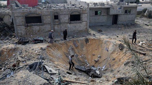 فلسطينيون يفحصون حفرة ناتجة عن غارة اسرائيلية خلال القتال مع حركات فلسطينية، في رفح، جنوب قطاع غزة، 14 نوفمبر 2018 (Said Khatib/AFP)