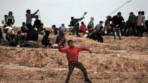 متظاهر فلسطيني يستخدم مقلاع لإلقاء الحجارة على القوات الإسرائيلية خلال مظاهرة في 16 نوفمبر / تشرين الثاني 2018، على المشارف الشرقية لمدينة غزة، بالقرب من الحدود مع إسرائيل. (Mahmud Hams/AFP)