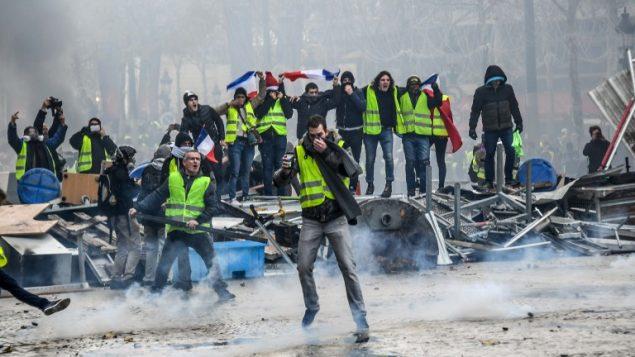 متظاهرو 'السترات الصفراء' خلال اشتباكات مع الشرطة في ميدان الكونكورد في باريس، 24 نوفمبر 2018 (BERTRAND GUAY / AFP)