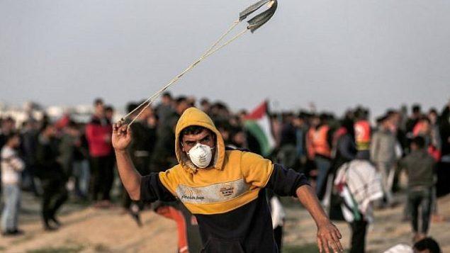 متظاهر فلسطيني يقذف حجراً باتجاه القوات الإسرائيلية خلال اشتباكات على طول الشريط الحدودي مع قطاع غزة شرق مدينة غزة في 30 نوفمبر / تشرين الثاني 2018. (Mahmud Hams/AFP)