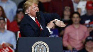 الرئيس الأمريكي دونالد ترامب ينظر إلى ساعته مع الاقتراب من اختتام تجمع انتخابي الإثنين، 5 نوفمبر، 2018، في كيب جيراردو بولاية ميزوري الامريكية. (AP Photo/Jeff Roberson)