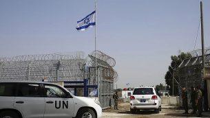 يفتح جندي إسرائيلي البوابات الحدودية أثناء دخول مركبة تابعة للأمم المتحدة إلى سوريا عند معبر القنيطرة في مرتفعات الجولان، الاثنين 15 أكتوبر، 2018. (AP Photo / Ariel Schalit)