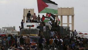 متظاهرون فلسطينيون يلوحون بالإعلام الفلسطينية أثناء ركوب شاحنة مليئة بالإطارات بالقرب من السياج الحدودي بين قطاع غزة وإسرائيل خلال مظاهرة في مدينة غزة، الجمعة، 26 أكتوبر، 2018.  (AP/Adel Hana)