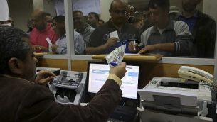 موظف حكومي فلسطيني لدى حماس يوقع من اجل الحصول على 60% من اجره المتأخر بينما ينتظر اخرون، في مكتب البريد المركزي في غزة، 9 نوفمبر 2018 (AP/Adel Hana)