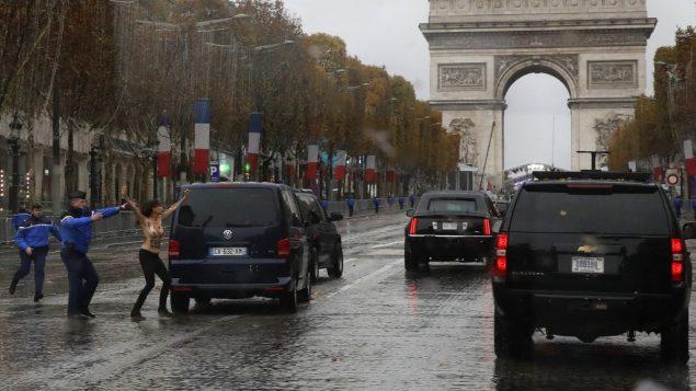 عناصر شرطة فرنسيون يلاحقون ناشطة عارية الصدر اندفعت نحو موكب الرئيس الامريكي دونالد ترامب في جادة الشانزيليزيه في باريس، 11 نوفمبر 2018 (AP Photo/Jacquelyn Martin)