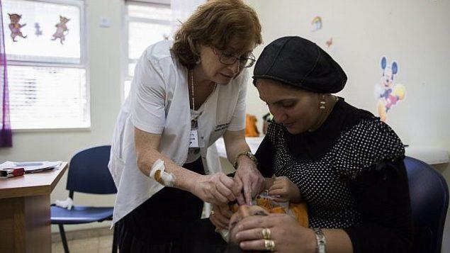 تطعيم طفل في عيادة طفولة مبكرة في القدس في 18 أغسطس 2013. (Yonatan Sindel / Flash90)