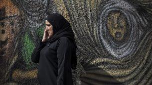 سيدة فلسطينية تتكلم بهاتف خليوي في الضفة رام الله، 28 اكتوبر 2014 (Hadas Parush/Flash90)