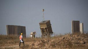 أحد المشغلين يمر من  أمام بطارية لنظام الدفاع الصاروخي 'القبة الحديدية' في مدينة سديروت في جنوب إسرائيل، 29 مايو، 2018.  (Yonatan Sindel/Flash90)