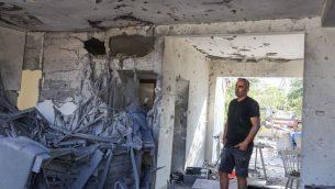 رجل يقف داخل منزل اصيب بصاروخ اطلق من قطاع غزة، في مدينة اشكلون جنوب اسرائيل، 13 نوفمبر 2018 (Nati Shohat/Flash90)