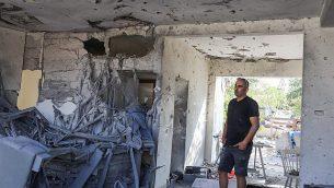 رجل يقف داخل منزل أصيب بصاروخ تم إطلاقه من قطاع غزة في مدينة أشكلون في جنوب إسرائيل، 13 نوفمبر، 2018. (Nati Shohat/Flash90)