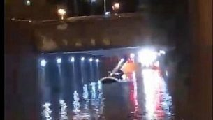 صورة شاشة من فيديو يظهر رجال اطفاء ينقذون رجل علق داخل سيارته داخل ممر تحتي ممتلئ بالمياه في حيفا، 24 نوفمبر 2018