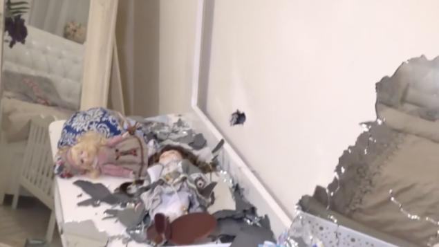 دمى على خزانة ملابس بجانب ثقب الذي تسببت فيه شظية صاروخ في جدار غرفة نوم في منزل في نتيفوت، 12 نوفمبر 2018 (Hadashot TV news)