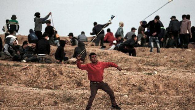 متظاهر فلسطيني يستخدم المقلاع لإلقاء حجارة على القوات الإسرائيلية خلال تظاهرة في 16 نوفمبر، 2018، على الأطراف الشرقية لمدينة غزة، بالقرب من الحدود مع إسرائيل.  (Mahmud Hams/AFP)