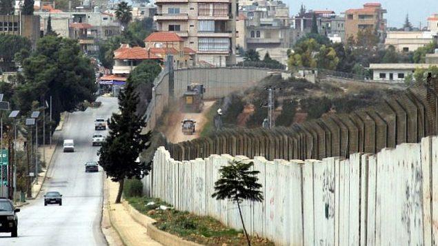 هذه الصورة تم التقاطها في 4 ديسمبر، 2018 من قرية كفركلا في جنوب لبنان وتظهر الحدود مع إسرائيل، مع مركبات إسرائيلية تسير من يمين الجدار ومركبات تابعة للأمم المتحدة ومركبات لبنانية تسير من يساره. (Ali DIA / AFP)
