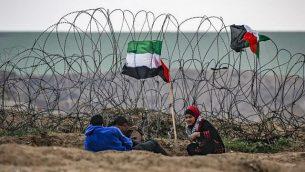 شبان فلسطينيون يجلسون بجانب علم فلسطيني بالقرب من السياج الشائك على طول الحدود مع إسرائيل شرق مدينة غزة أثناء تظاهرة حدودية في 7 ديسمبر/كانون الأول 2018. (Said Khatib/AFP)