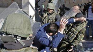 قامت قوات الأمن الفلسطينية تضرب أحد أنصار حماس أثناء محاولتها تفريق مظاهرة بمناسبة الذكرى الحادية والثلاثين لتأسيس الجماعة في الخليل في 14 ديسمبر 2018. (Hazem Bader/AFP)